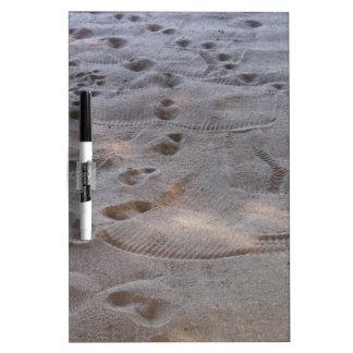 huellas en el tablero blanco de la arena