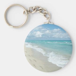 Huellas en la playa de Sandy blanca aguamarina es Llavero