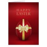 Huevo de Pascua rojo con la tarjeta de felicitació