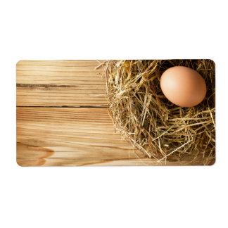 Huevo en jerarquía del heno en fondo de madera de  etiqueta de envío