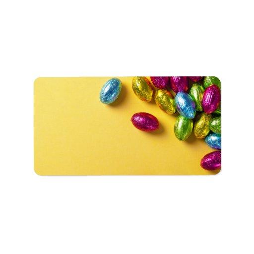 Huevos de Pascua coloridos del chocolate en el pap Etiqueta De Dirección