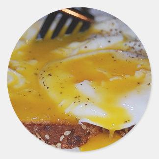 Huevos escalfados en el pegatina de la tostada