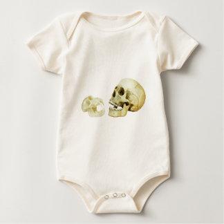 Human and monkey skull opposite of each other baby bodysuit