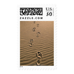 Human footprints on sandy beach postage
