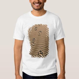 Human footprints on sandy beach T-Shirt