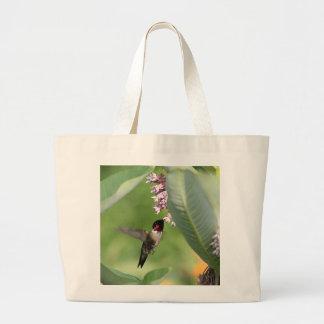Hummingbird feeding on pink flowers large tote bag