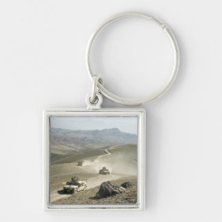 Humvees traverse rugged mountain roads keychain