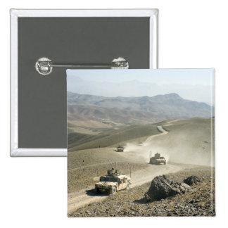 Humvees traverse rugged mountain roads pinback button