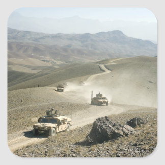 Humvees traverse rugged mountain roads square sticker