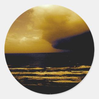 huracán de la tormenta que se acerca a la playa etiqueta redonda