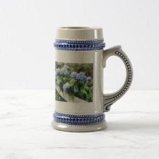 Hydrangea azul en la cerca blanca tazas
