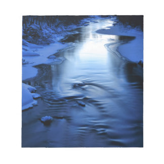Icy and snowy river with winter blue notepad