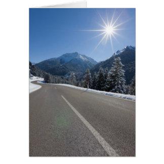 Idyllic empty road thrugh a winter landscape, card