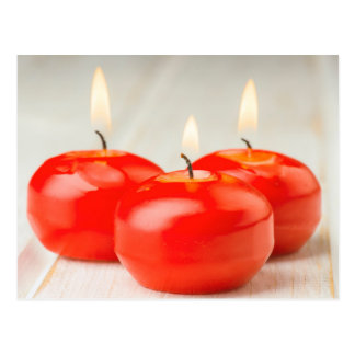 Ignited and aligned red candles postcard