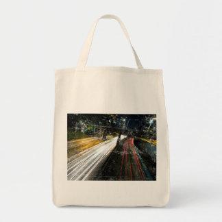 Imagen de una autopista sin peaje en la noche con bolsa tela para la compra