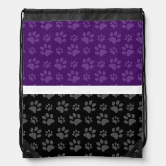 Impresión negra y púrpura de la pata del perro mochilas