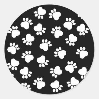 Impresiones blancos y negros de la pata de la pegatina redonda