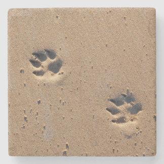 Impresiones de la pata del perro en una playa posavasos de piedra
