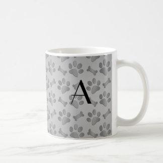 Impresiones grises de la pata del perro del monogr taza de café