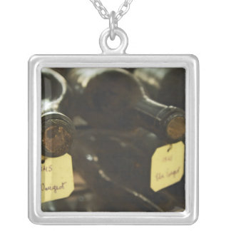 In the underground wine cellar: lying bottles in square pendant necklace