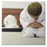 Inclinación del equipo del karate del muchacho que tejas