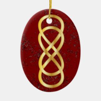 Infinito doble en oro en el mármol rojo ornamento de navidad