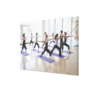 Instructor de la yoga enseñando a una clase de impresión en lienzo
