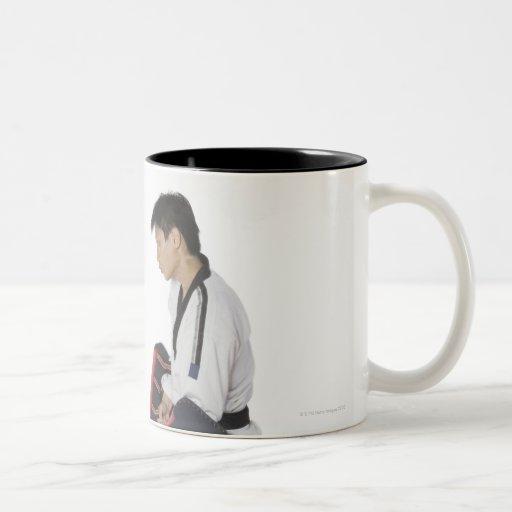 Instructor de sexo femenino del karate que enseña taza de dos tonos