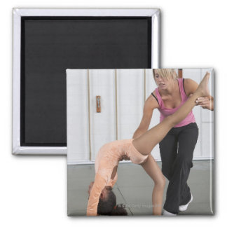 instructor helping girl with her floor exercises 2 inch square magnet