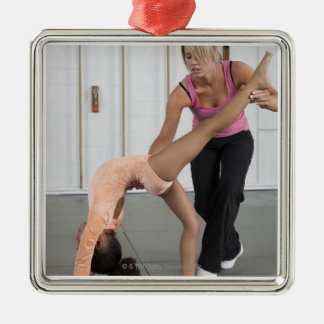 instructor helping girl with her floor exercises metal ornament