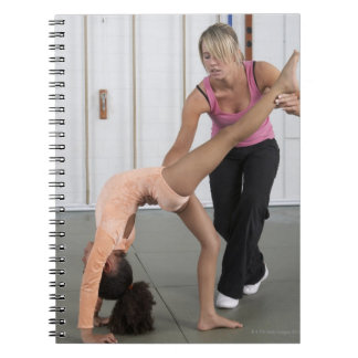 instructor helping girl with her floor exercises note book