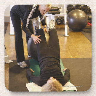 Instructor helps senior client with stretches drink coaster
