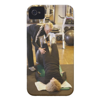 Instructor helps senior client with stretches iPhone 4 case