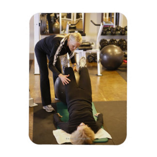 Instructor helps senior client with stretches magnet
