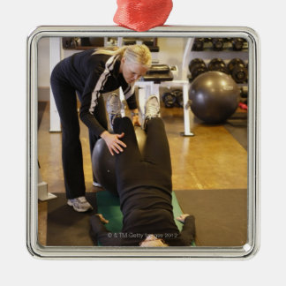 Instructor helps senior client with stretches metal ornament