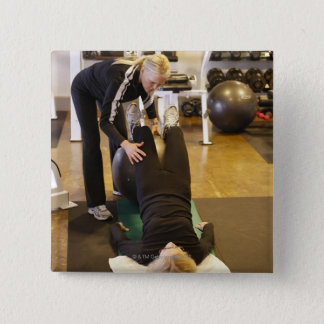 Instructor helps senior client with stretches pinback button