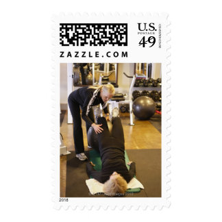 Instructor helps senior client with stretches stamps