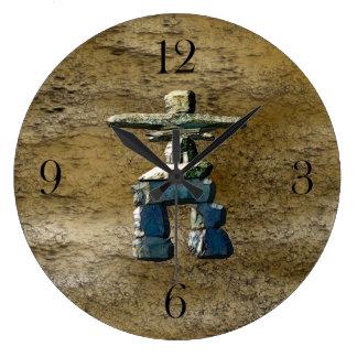 Inukshuk y reloj de la textura de la roca