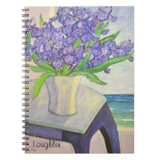 Iris en florero por el cuaderno de la ventana