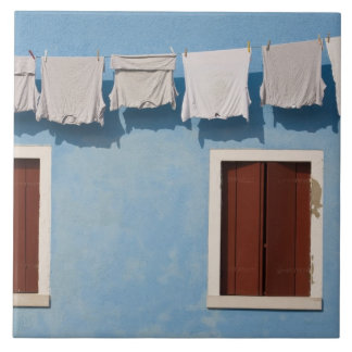 Italy, Burano. Hanging laundry and windows along Tile