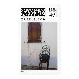 Italy, Sardinia, Castelsardo. Cafe chairs. Postage
