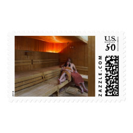 Italy, Tuscany, Young couple relaxing in sauna Postage