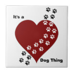 """It&#39;s A Dog Thing Heart and Paw Print Tile<br><div class=""""desc"""">As a dog lover,  we know that with a wag of their tail or a furtive look our dogs leave their mark on our hearts. Customize this design by adding your own text or changing the text in the design.</div>"""