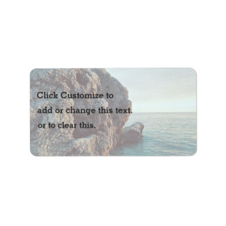 Jagged rock cliff faces water address label
