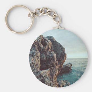 Jagged rock cliff faces water basic round button keychain