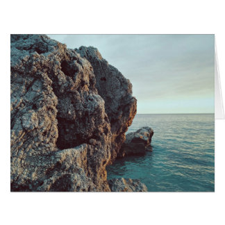Jagged rock cliff faces water large greeting card