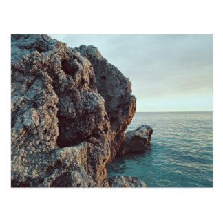 Jagged rock cliff faces water postcard