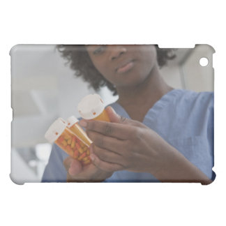Jamaican female nurse checking pill bottles iPad mini covers