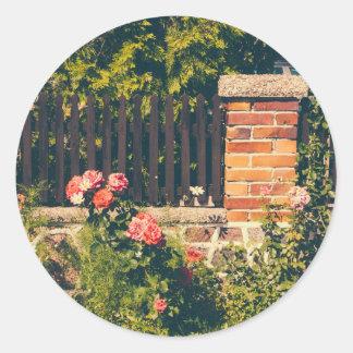 Jardín idílico con los rosas, cerca de madera etiqueta redonda