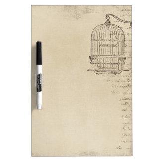 Jaula de pájaros del vintage con la vieja escritur pizarra